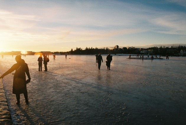 Locals and tourists enjoying the frozen pond in Reykjavik, Iceland